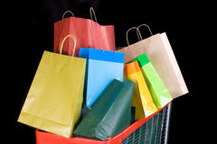 Shopping cart full of gifts on black background Royalty Free Stock Photo