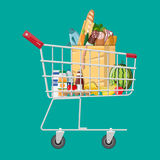 Shopping cart full of groceries products. Grocery store. Supermarket. Fresh organic food and drinks. Vector illustration in flat style Stock Photography