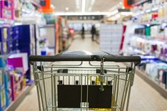 Shopping cart full of grocery on blurred supermarket aisle. Stock Photo