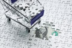 Shopping cart full of jigsaw puzzle on money dollar background,. Business solution concept ,key for success Royalty Free Stock Images