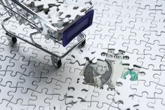 Shopping cart full of jigsaw puzzle on money dollar background,. Business solution concept ,key for success Stock Photos