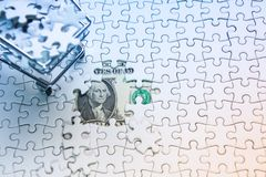 Shopping cart full of jigsaw puzzle on money dollar background,. Business solution concept ,key for success Royalty Free Stock Photos