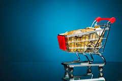 Shopping cart full of money. On blue background Royalty Free Stock Image