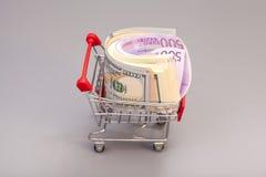 Shopping cart full of money (dollar, euro) Stock Images