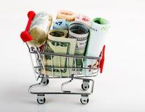 Shopping cart full of money (dollar, euro ). Shopping cart full of money (dollar, euro). Multi currency basket concept Stock Image