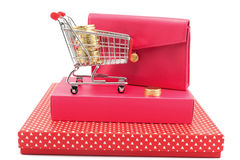 Gift conceptional objects. Shopping cart full ofcoin shape chocolates on gift boxes besides a red wallet Royalty Free Stock Photo