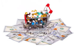 Shopping cart full with pills and capsules over dollar bills Royalty Free Stock Photo