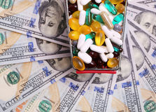 Shopping cart full with pills over dollar bills Royalty Free Stock Images