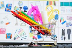 Shopping cart full of school tools on the keyboard, online shopping concept.  stock photos