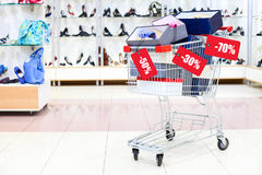 Shopping cart full of shoe boxes with sale tag Royalty Free Stock Images