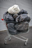 Shopping cart with garbage bags Royalty Free Stock Images