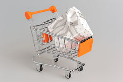 Shopping cart with gift box on gray Stock Photography