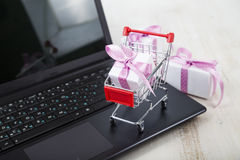 Shopping cart with gift box on laptop. Stock Photos