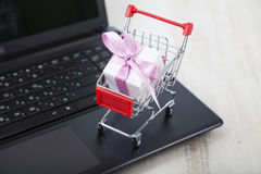 Shopping cart with gift box on laptop. Concept of shopping onlin Stock Image