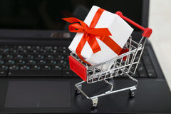 Shopping cart with gift box on laptop. Concept of shopping onlin Stock Photography