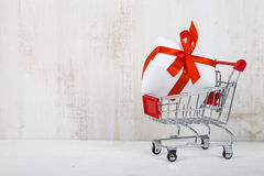 Shopping cart with gift box on a light wooden background. Royalty Free Stock Photos