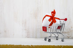 Shopping cart with gift box on a light wooden background Stock Photo