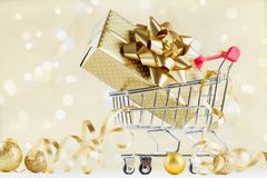Shopping cart with gift or present box on golden bokeh background. Christmas and New year sale concept. royalty free stock photos