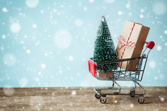Shopping cart with gift or present and fir tree on snowy effect background. Christmas and New year sale concept. Greeting card.