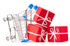 Shopping cart with gifts. Crashed shopping cart with a lot of gifts cut out from white Royalty Free Stock Photo