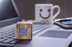 Shopping cart graphic. Wooden block with shopping cart graphic on laptop keyboard with happy face mug background Stock Image