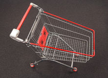 Shopping cart on a gray carpet Royalty Free Stock Image