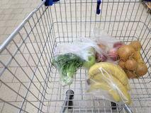 Shopping cart with grocery at supermarket Stock Images