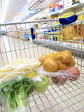 Shopping cart with grocery at supermarket Stock Image