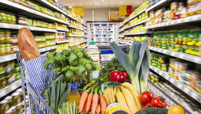 Shopping cart with healthy foods in the supermarket. Detail of a shopping cart with fruit and vegetables between goods shelves in the supermarket royalty free stock photography