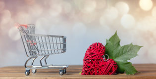 Shopping cart and heart shape toy with leaves Stock Photos