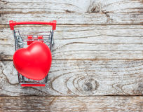 Shopping cart and heart on wood Stock Photos