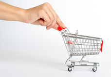 Shopping cart with humans hand Royalty Free Stock Photos