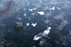 Shopping cart on ice. A caddy on the frozen surface of a lake stock images