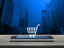Shopping cart icon on modern smart phone screen on wooden table Stock Photo