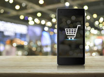 Shopping cart Icon on modern smart phone screen on wooden table Stock Image