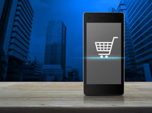 Shopping cart icon on modern smart phone screen on wooden table Stock Images