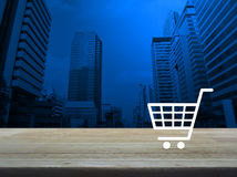 Shopping cart icon on wooden table over modern office city tower Royalty Free Stock Photography