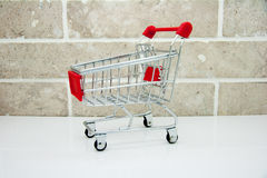 A shopping cart Isolated on brick background Stock Photo