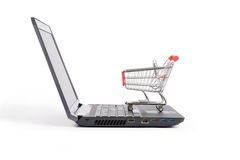 Shopping cart on laptop, side view Royalty Free Stock Photo