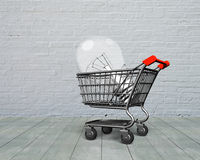 Shopping cart with large light bulb. On brick wall and wooden floor background stock images