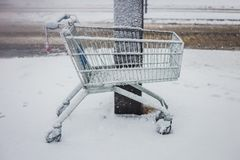 Shopping cart left in front of a shopping center, in the snow. Stock Photos