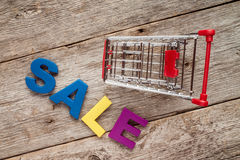 Shopping cart and letters spelling SALE Royalty Free Stock Images