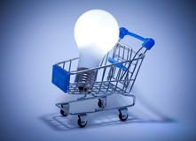 Shopping cart with light bulb. Stock Photo
