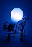 Shopping cart with light bulb in blue light. Royalty Free Stock Photography