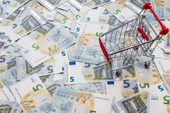 Shopping cart and many five euro banknotes Royalty Free Stock Photo