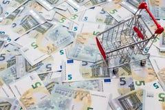 Shopping cart and many five euro banknotes Royalty Free Stock Photo