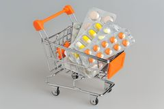 Shopping cart with medical supplies on gray Stock Photo