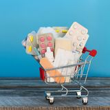Shopping cart with medication. On a blue background Stock Photo