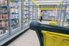 A shopping cart in the middle of a supermarket royalty free stock image