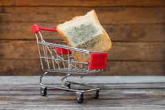 Shopping cart with mold on bread. The concept of selling spoiled food. Stock Image